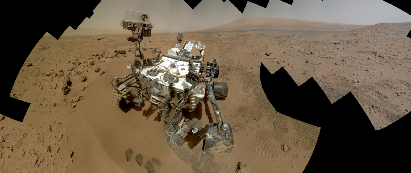 Image of the Curiosity Rover on the Martain surface. In this composite photograph we see the rover perched on the rusty-red Martian soil, with a series of hills and a dusty colored sky in the background. The outline of this image is jagged due to the effects of combining the individual frames into a single montage.
