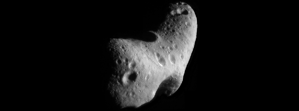 Looking Down on the North Pole of Eros. In this image looking down the length of this somewhat boomerang-shaped asteroid, many craters and surface features can be seen.