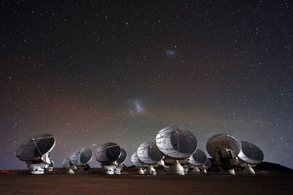 Image of the Atacama Large Millimeter/Submillimeter Array (ALMA) observatory at night. In the foreground are the many radio telescopes of the array. In the background above the array are two diffuse patches of light. The larger patch of light close to the horizon is the Large Magellanic Cloud. The smaller patch above and to the right is the Small Magellanic Cloud. A few stars from our Milky Way are scattered across the sky.