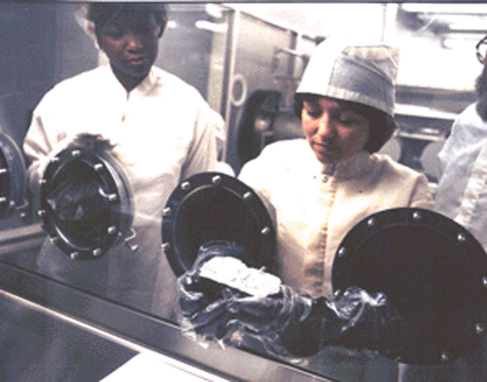 """Photograph of Technicians Examining a Lunar Sample. Two scientists look at a Moon rock through the glass of a scientific """"glove box""""."""