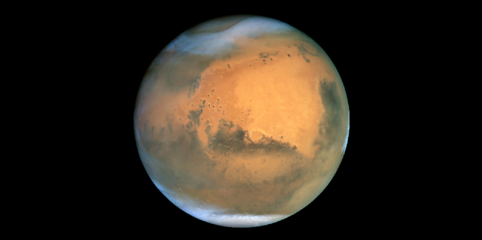 HST image of Mars. The hemisphere seen in this image shows dark regions on the lower half, a large reddish zone near the center, a polar cap and some clouds at the bottom, and a large area of wispy clouds near the top.