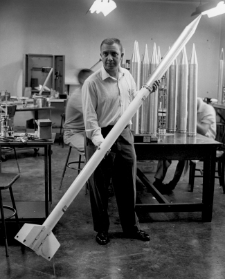 """Photograph of James Van Allen holding a small rocket, which was part of a """"rockoon""""."""