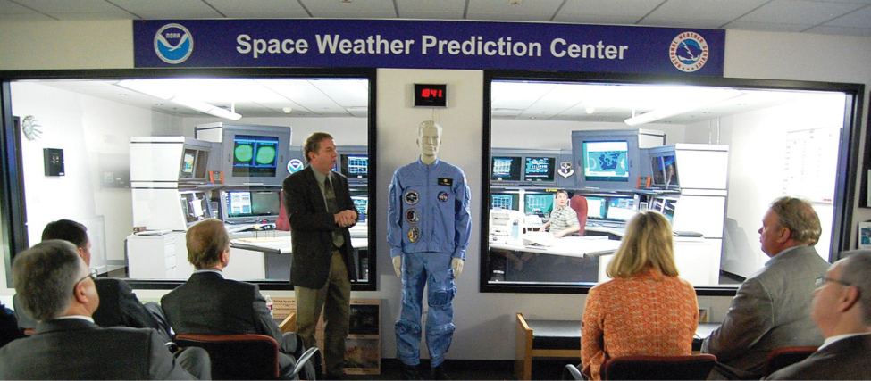"""An image of several seated people in a room with a banner reading """"Space weather prediction Center."""" At the front of the room a person stands and addresses the seated people."""
