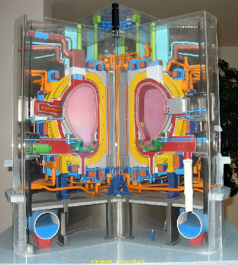 Cutaway Model of the ITER Design. In the center of this model are two pink kidney shaped areas that represents the hollow chamber wherein the particles will travel. The bright yellow areas surrounding the chamber are the superconducting magnets. Surrounding these two structures are a myriad of pipes, wires, conduits and other components of this highly complex machine.
