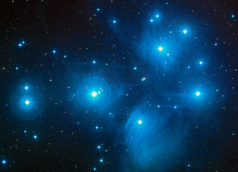 The Pleiades. The light from the bright, blue stars of this cluster reflects off of the nearby dust clouds, giving the appearance of streetlamps on a foggy night.