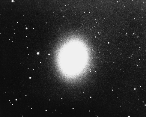 Dwarf Elliptical Galaxy M32. This companion to the Andromeda Galaxy is, like most ellipticals, a featureless and uniform oval of light. Note that individual stars can be seen at the edges where the density of stars declines.