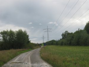 A high-voltage traction power line is shown to the side of a roadway. The power line in the photo has two transmission poles supporting the cables.