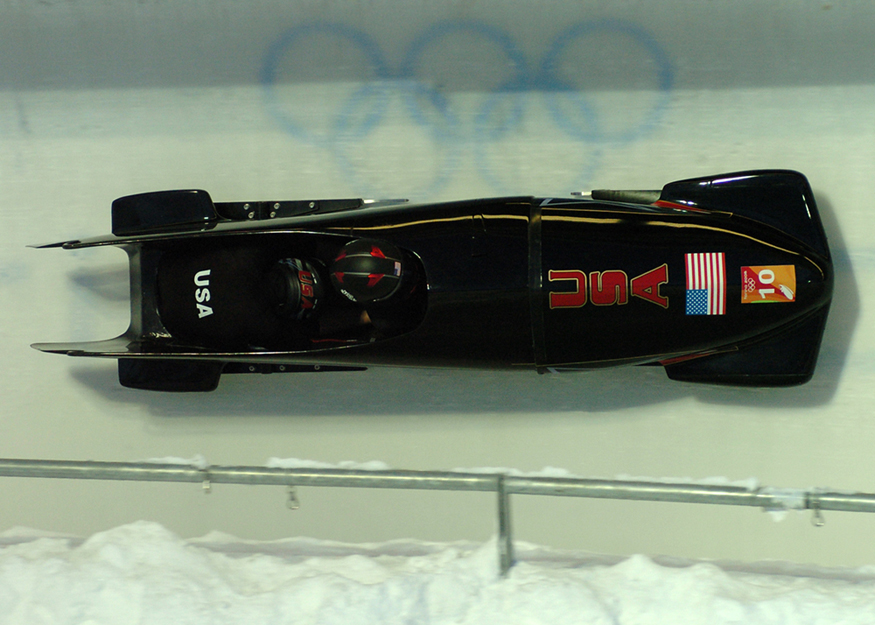 A two-person team in a bobsled race. The bobsled has an aerodynamic design and smooth runners so it can go as fast as possible.