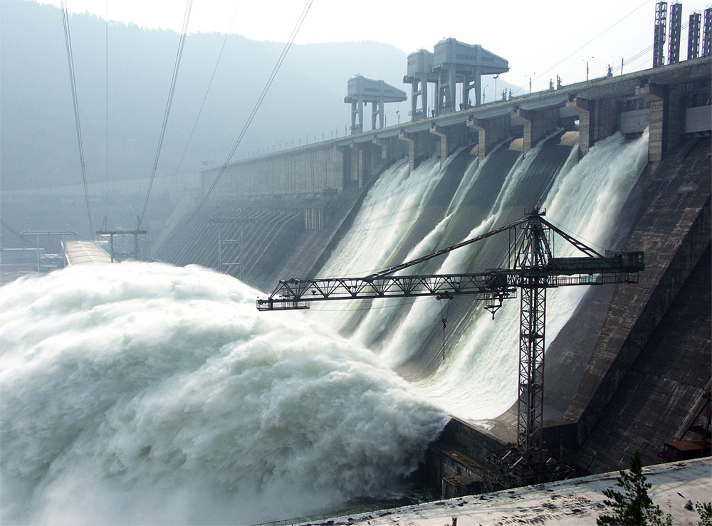 A dam with water flowing down its gates.