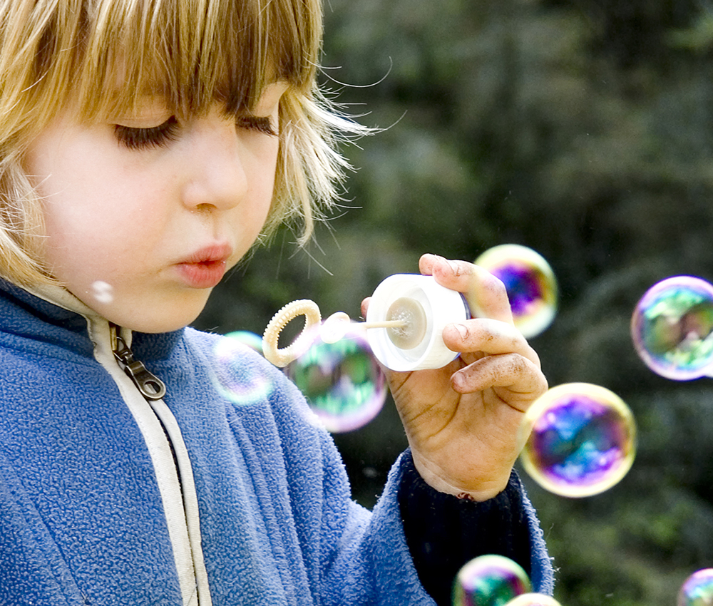 The soap bubbles that the child blows into the air maintain their shape because of the attractive force between the molecules of the soap bubble.