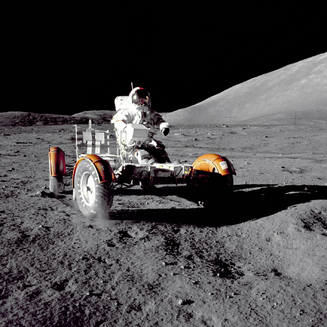Photograph of the lunar rover on the Moon. The photo looks like it was taken at night with a powerful spotlight shining on the rover from the left: light reflects off the rover, the astronaut, and the Moon's surface, but the sky is black. The shadow of the rover is very sharp.