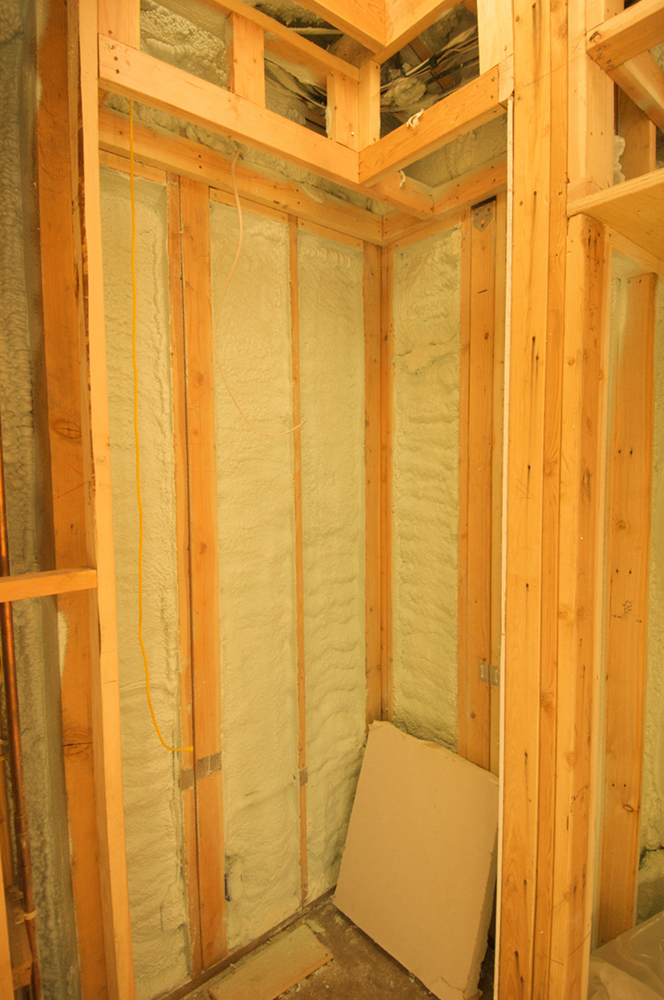 The figure shows an insulated wooden partition in a house. The partition is insulated because it encapsulates a cloth-type material.