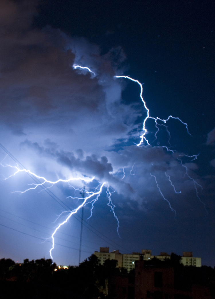The figure shows lightning strikes from thunderclouds above an urban area.