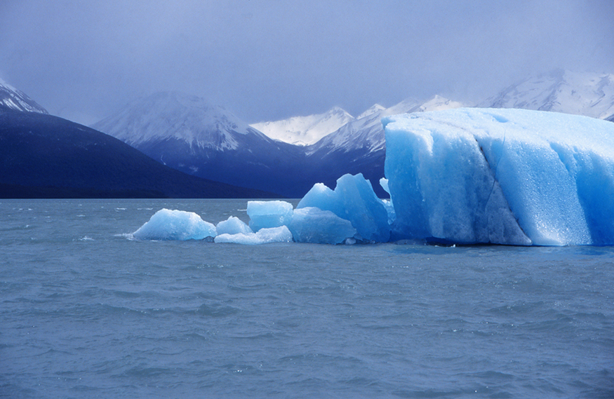 The figure shows some blue-colored icebergs floating in the water beneath snow-capped mountains and a cloudy sky. Some of the icebergs at front are melting.