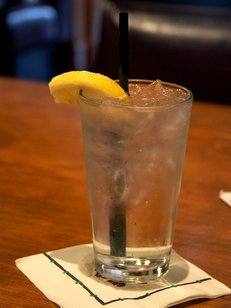 Photograph shows a glass of a beverage with ice cubes and a straw, placed on a paper napkin on the table. There is a piece of sliced lemon at the edge of the glass. There is condensate around the outside surface of the glass, giving the appearance that the ice is melting.