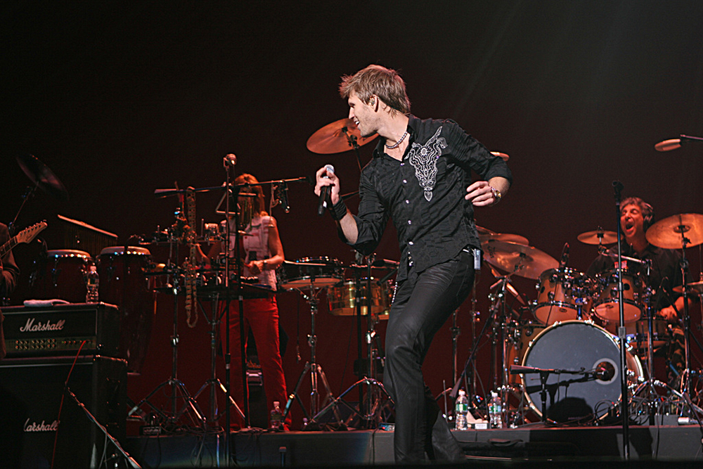 Photograph of a musical band with a person singing.