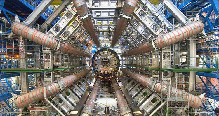 Inside part of the Large Hadron Collider; complex system of machinery and electronics, with a person for scale