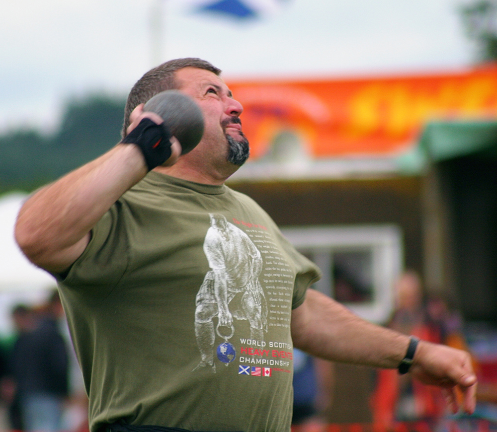 A close view of a shot-putter throwing the shot.