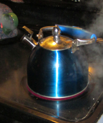 The photograph shows water boiling in a tea kettle kept on a stove. The water vapor is shown to emerge out of the nozzle of the kettle.