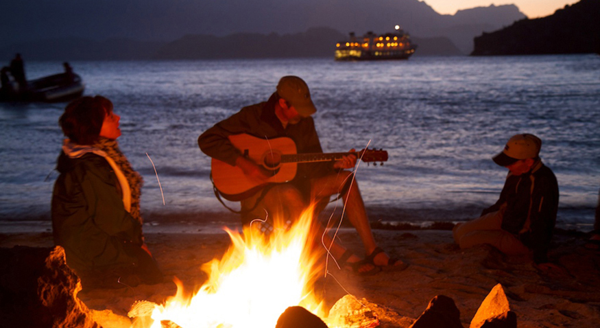 In the figure a couple and their son are sitting alongside a beach in the evening time, around a wood-lit fire. The man is playing a guitar.