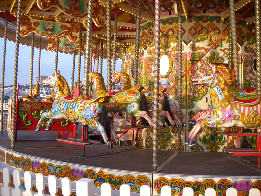 The figure shows a clock-wise rotating empty merry go round with iron bars holding the decorated wooden horse statues, four in each column.