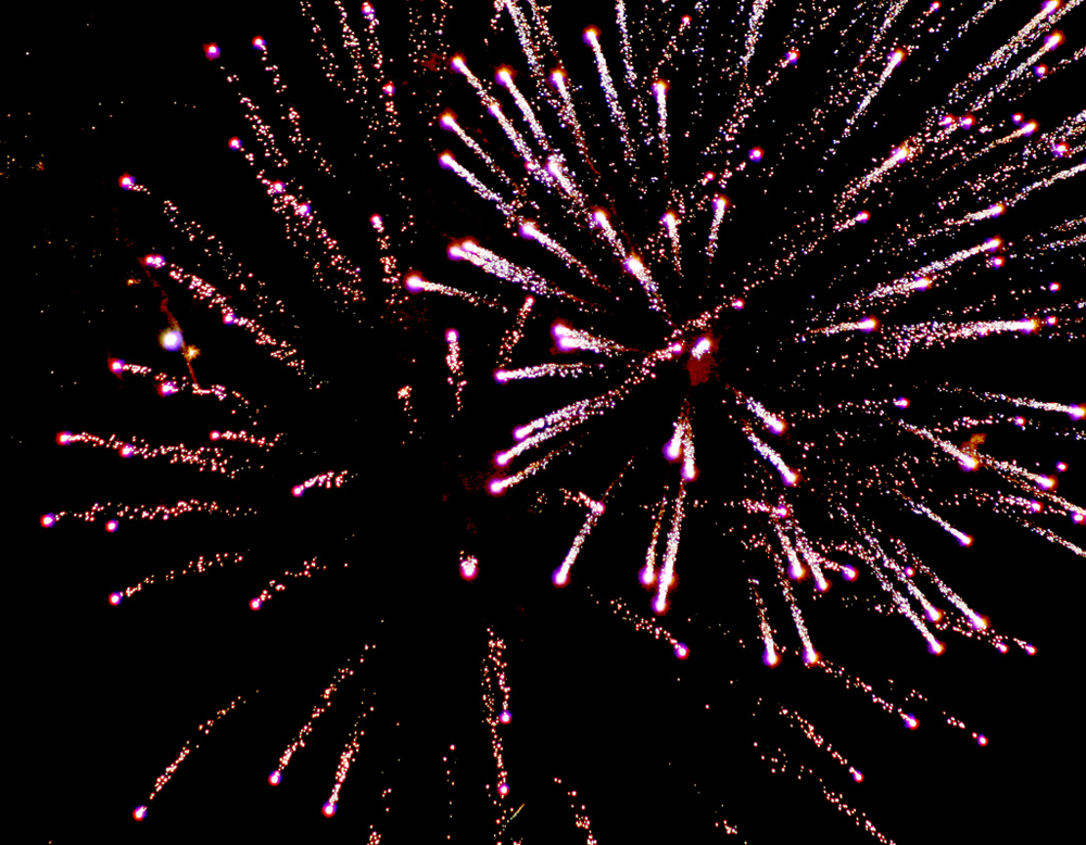 A photograph of a fireworks display in the sky.