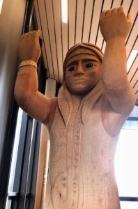 Welcome pole - wooden carving of woman with arms held up and open