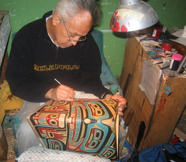 'Namgis master carver Bruce Alfred painting a bentwood box