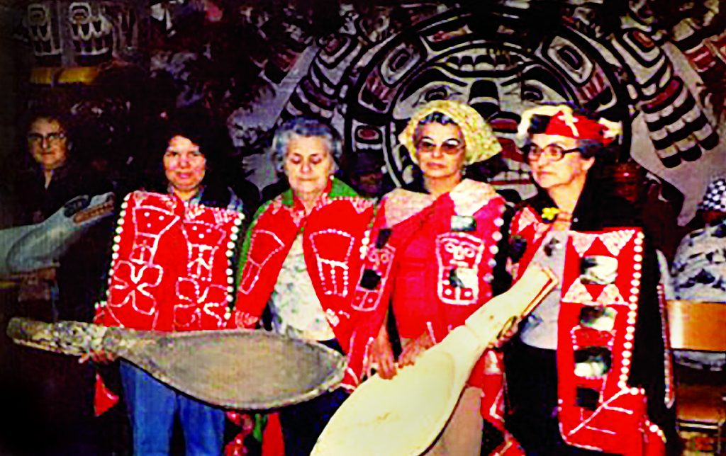 Arthur Dick's sister Daisy Joseph, daughter Gwi'molas Vera Newman and aunties, Ethel Alfred, Stella Sumners, and cousin Christine Taylor holding grease spoons and wolf feast dish at a T'łi'nagila (grease feast) he hosted