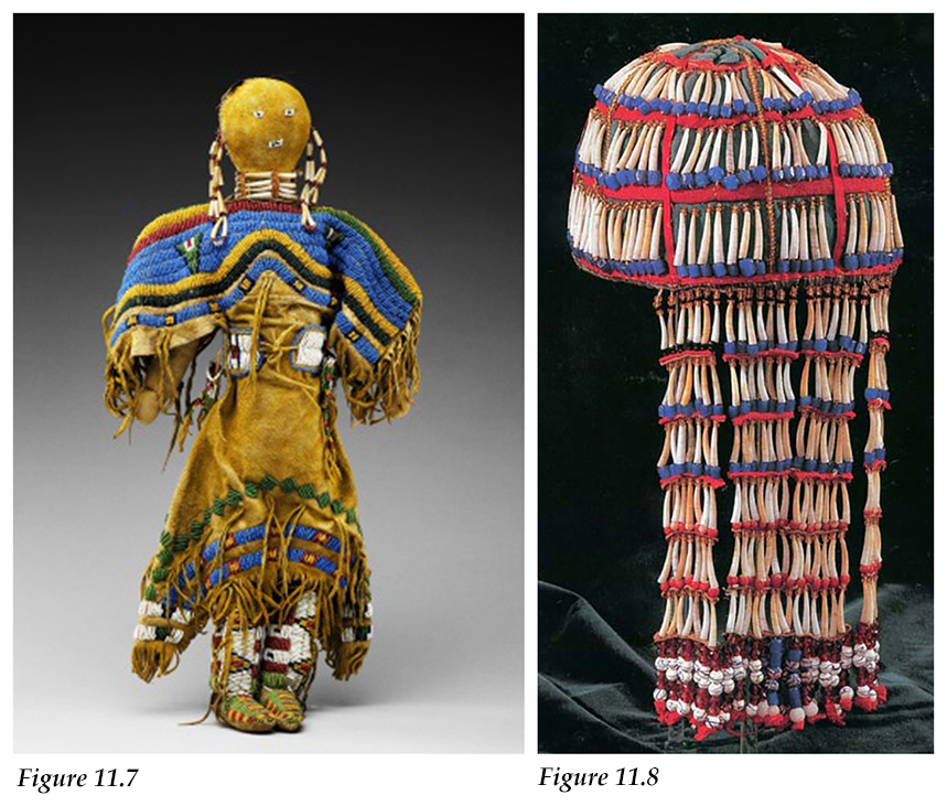 Dentalium shells dangle from the braids and form a necklace for a Sioux doll and beaded Tlingit headdress