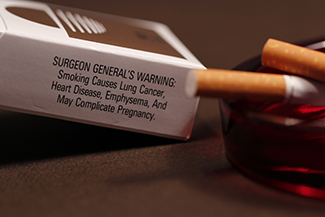 """A photograph shows pack of cigarettes and cigarettes in an ashtray. The pack of cigarettes reads, """"Surgeon general's warning: smoking causes lung cancer, heart disease, emphysema, and may complicate pregnancy."""""""
