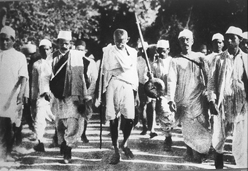 A photograph of Mohandas Gandhi is shown. There are several people walking with him.