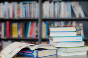 Photo of a stack of textbooks in front of a bookcase