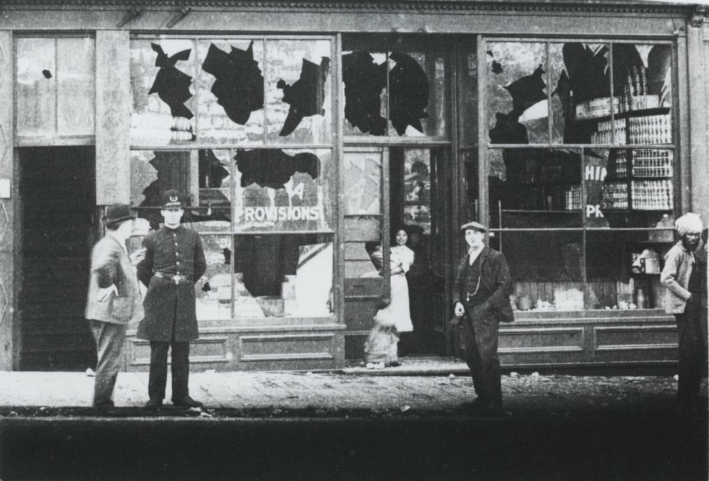 A photo of a damaged storefront resulting from a riot that targeted Chinese and Japanese businesses in Vancouver. There are a couple of people in the doorway of the damaged business, along with a policeman and a handful of bystanders on the sidewalk.