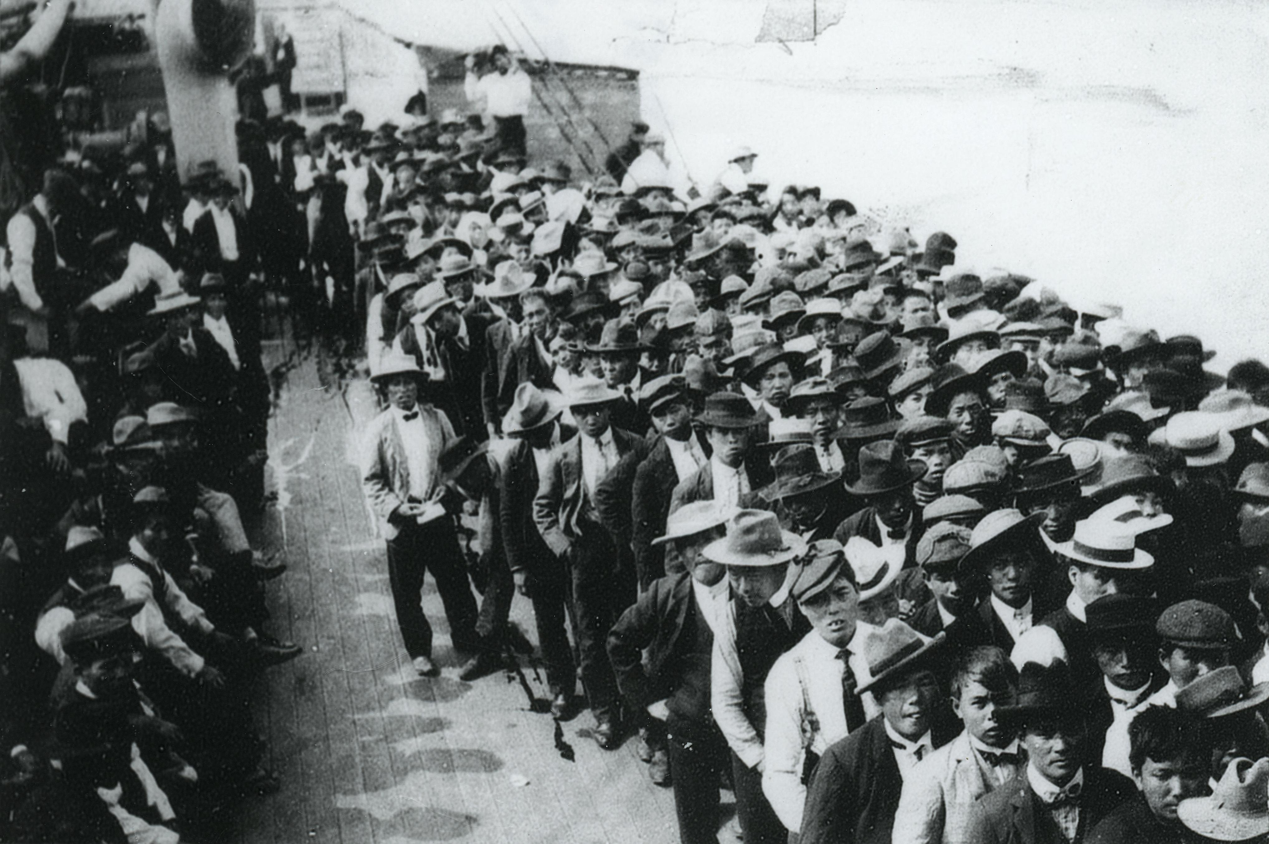 A photo depicting a large group of Japanese immigrants on the deck of the S.S. Kumeric at the port of Vancouver in 1907.