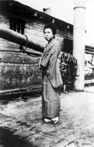 This photo is a full-body portrait of Japanese woman on the deck of the S.S. Kumeric.