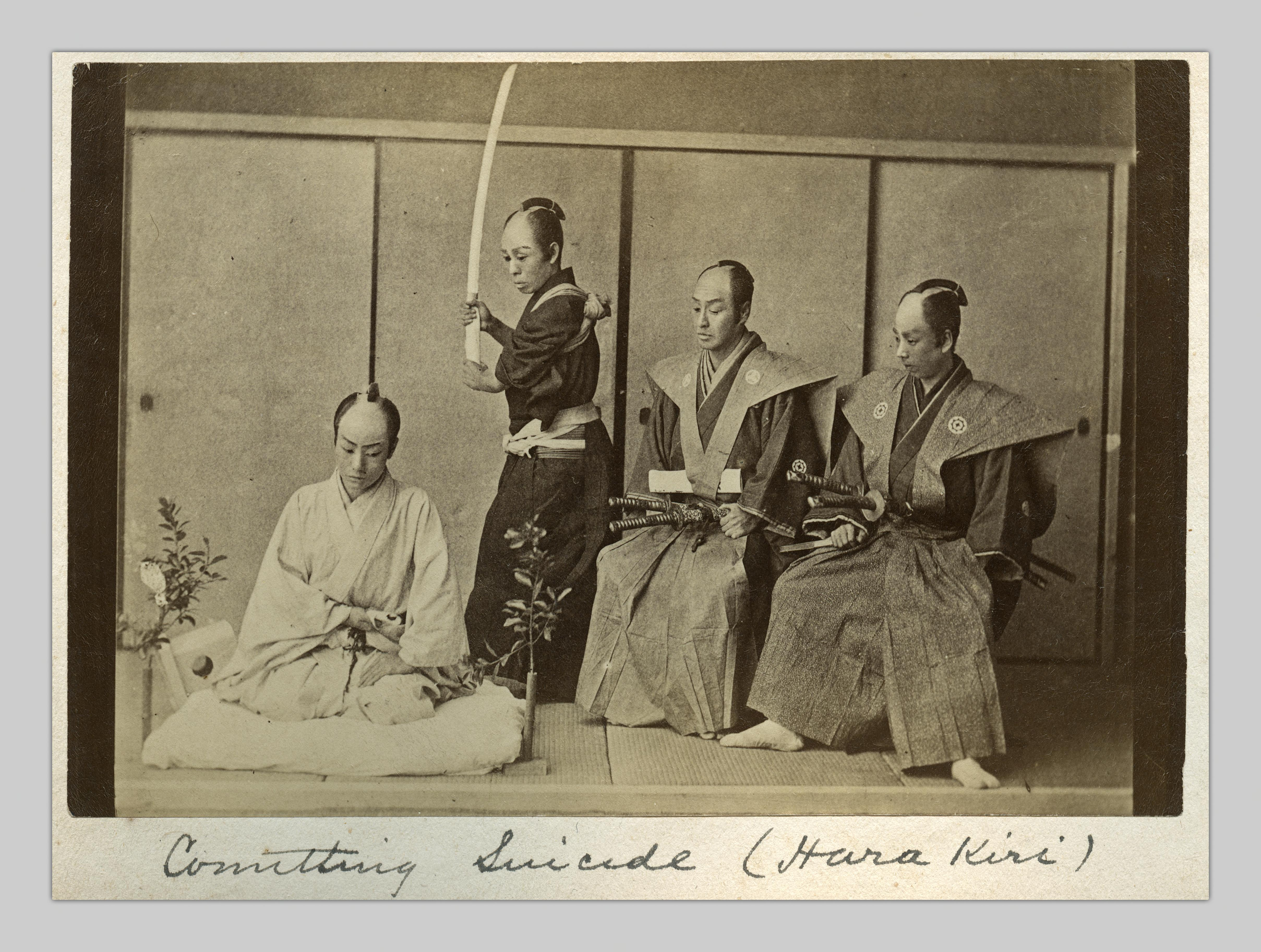 """A photograph by Ogawa Kazumasa entitled """"Committing Suicide (hara kiri)."""" In the photo, two official-looking man with sheathed swords are sitting to the right of two other figures, one standing with sword pointed upwards at the ready and the other seated on a cushion, looking downcast."""