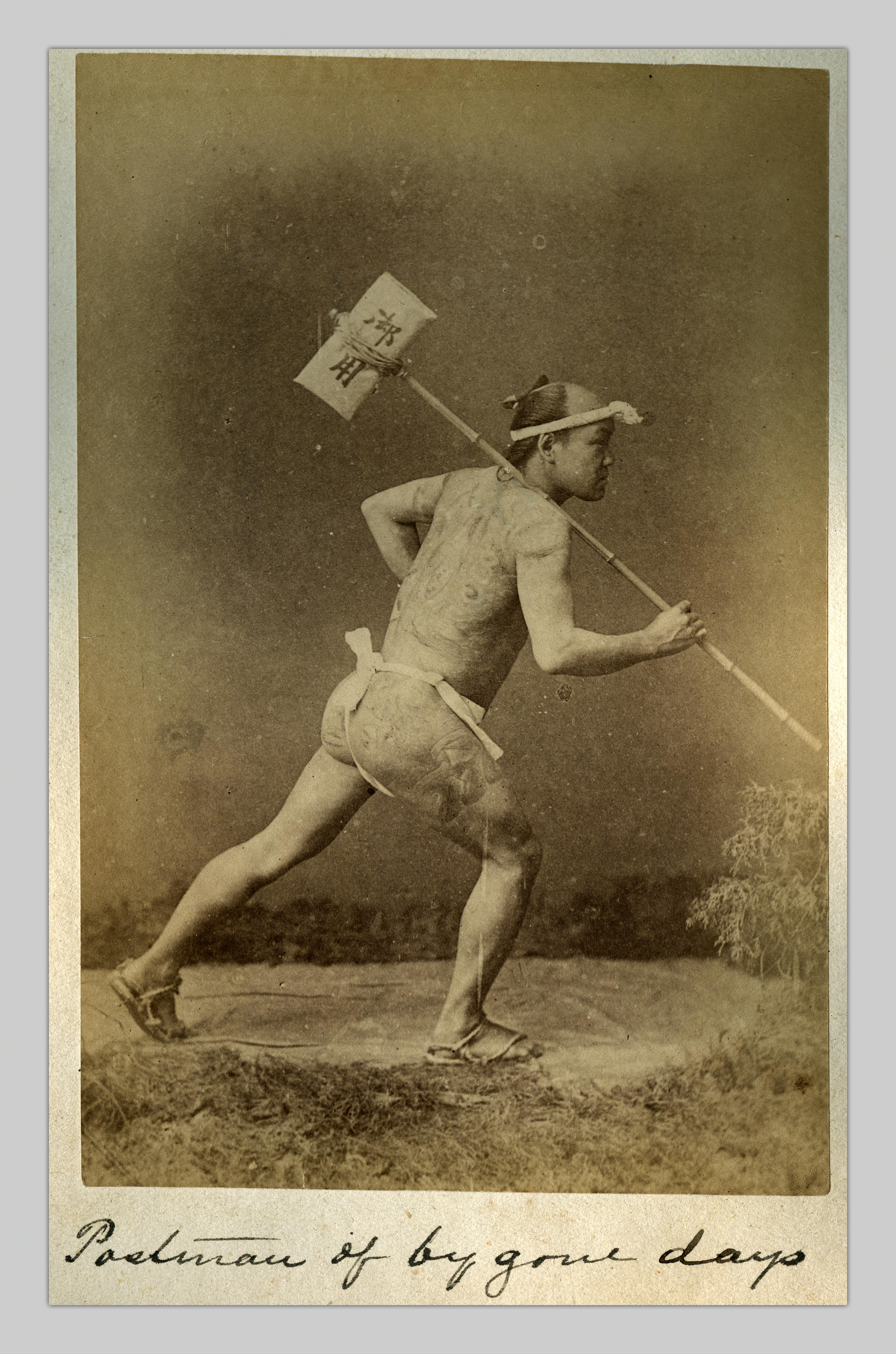 """A photograph by Tamamura Kōsaburō entitled """"Postman of bygone days."""" The figure in the photo is posing mid-step. Resting on his shoulder is a long bamboo pole with a bundle of mail tied tightly to the end."""