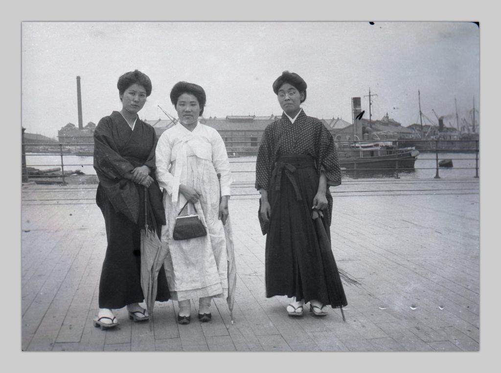 A photo by John Cooper Robinson of three Japanese women standing on Yokohama pier. The women are facing the camera.