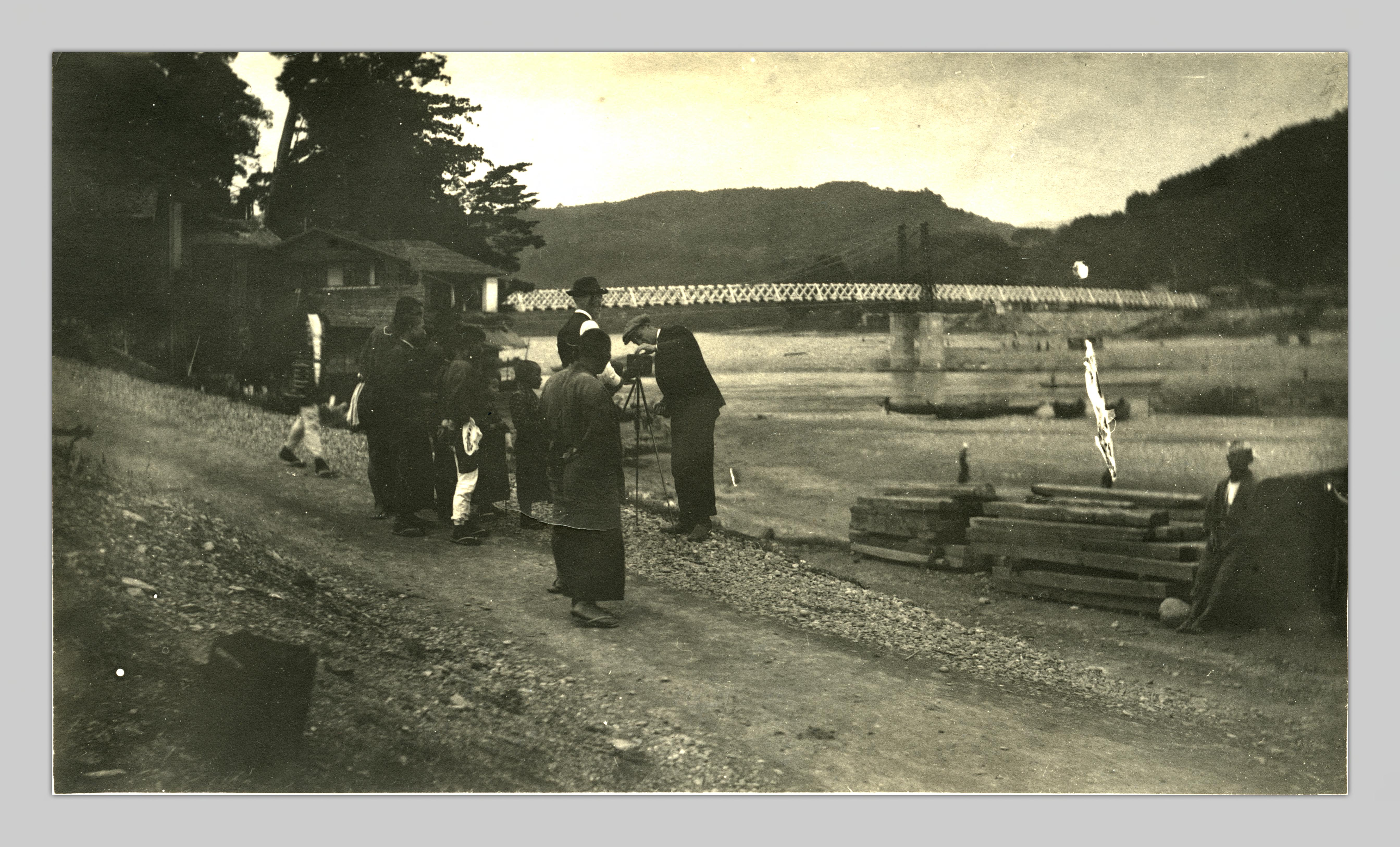 A wide shot of John Cooper Robinson and his unidentified companion adjusting a camera near a river. A bridge is visible in the background.