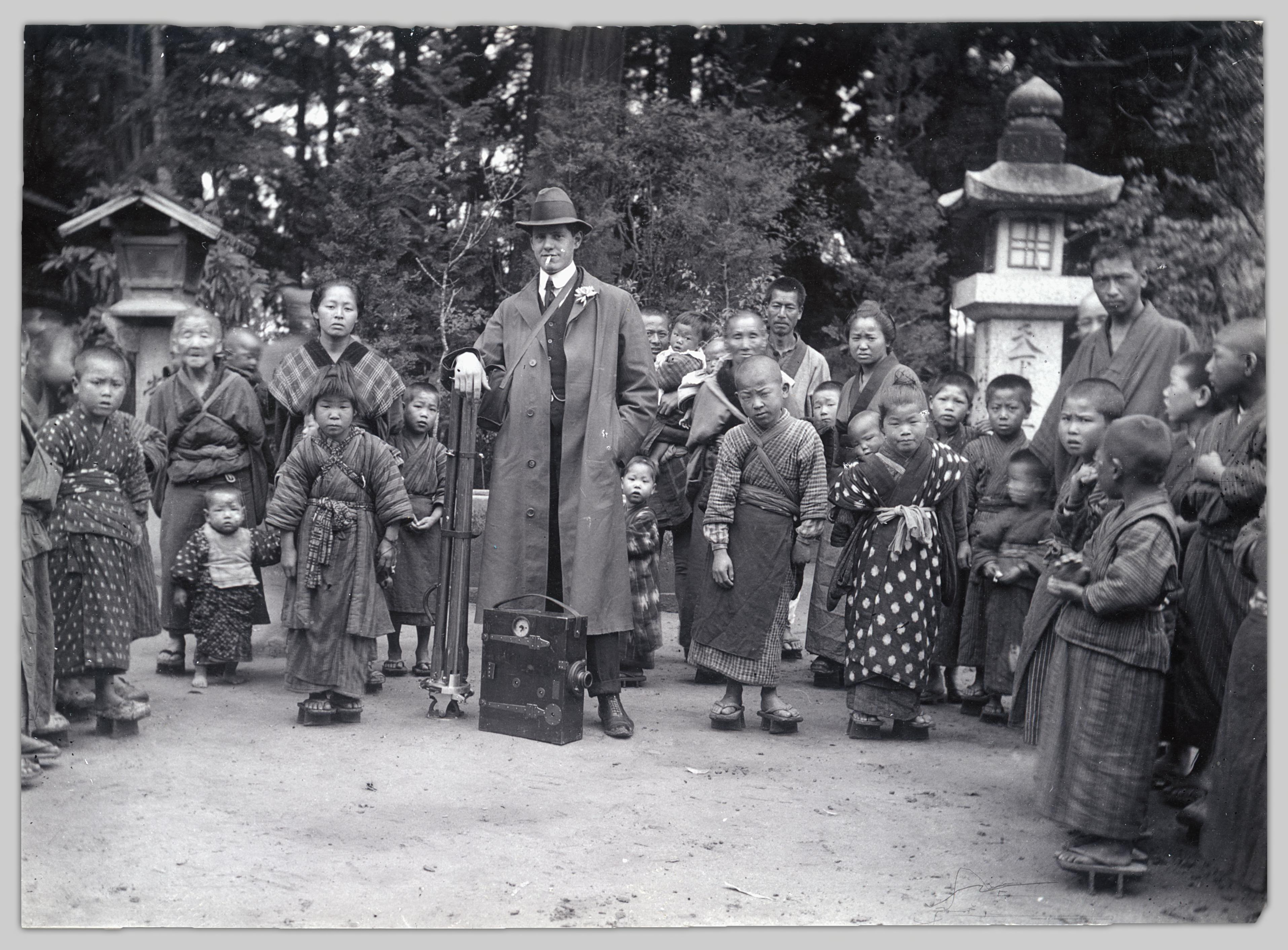 A photo of Cuthbert Robinson (John Cooper Robinson's son) posing with a large format camera, surrounded by Japanese children and guardian of various ages.