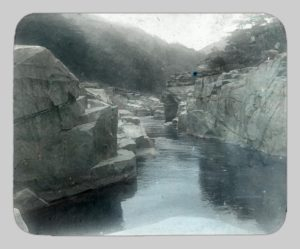 A colorized photograph of Kisō River by John Cooper Robinson. Striking rock formations buffer the river.