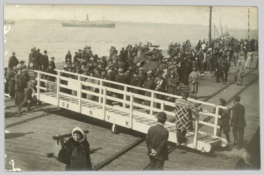 A photo by John Cooper Robinson of a crowd standing on Yokohama pier.