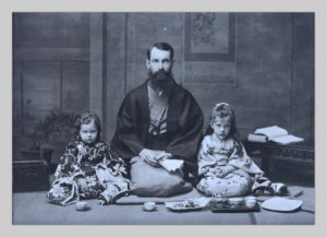 John Cooper Robinson with his young daughters Lucy and Hilde, a photograph by Miyashita Kin. They are seated on the floor in traditional Japanese garb.