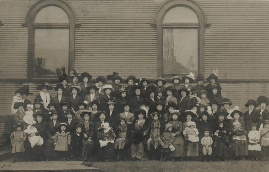 This photo depicts a sizable group of women and children posing in front of the Vancouver Japanese Buddhist Church building.