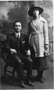 A portrait, dated to 1921, of a standing woman, Hanako Sato, and a seated man, Tsutae Sato. Hanako taught at the Vancouver Japanese Language School on Alexander Street.