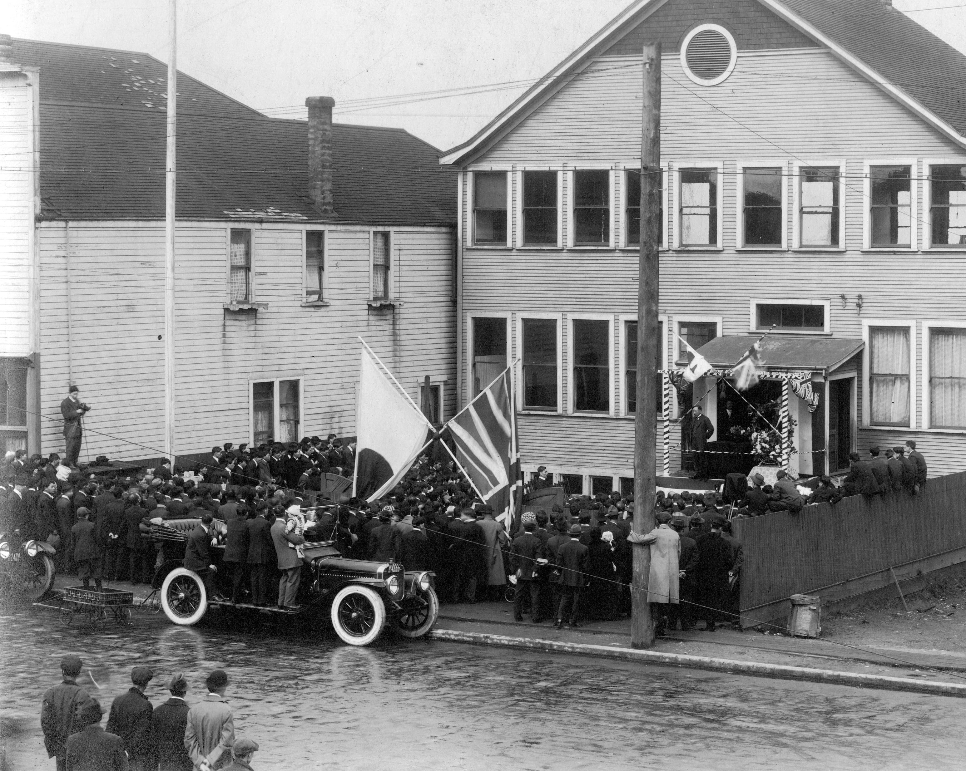"This photo depicts a large crowd of people in the front yard of the ""old"" school, gathered for an event involving a speech or discussion."