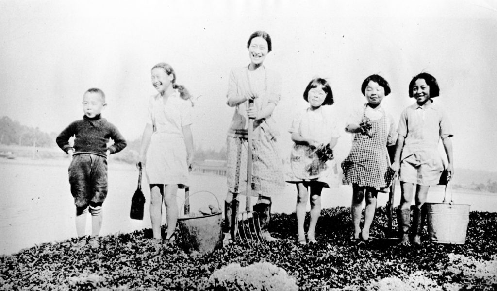 In this photo, Hanako Sato and a group of five smiling children at Vancouver Japanese Language School pose with a picnic basket and garden implements.