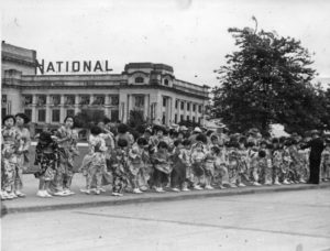 In this photo, a large group of girls wait along the sidewalk for the King and Queen outside the train station at Main Street and Terminal Avenue in Vancouver.