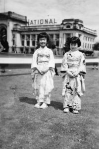 In this photo, two girls stand in the grass waiting for the King and Queen outside the train station at Main Street and Terminal Avenue in Vancouver.